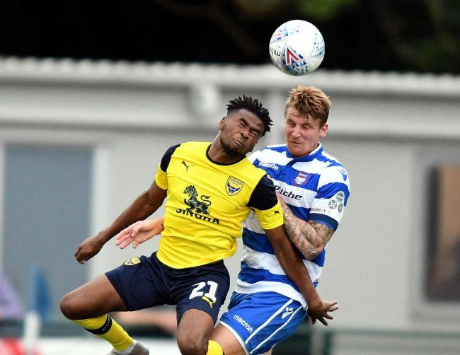 Oxford United goalscorer Malachi Napa challenges Oxford City captain Joe Oastler in the air  Picture: Mike Allen