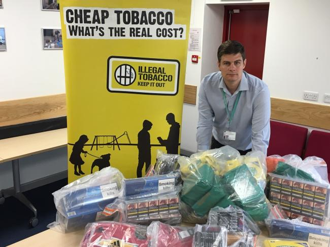 Jody Kerman of Oxfordshire Trading Standards with the haul of 3,500 counterfeit cigarettes seized in Benson. 			            Picture: Oxfordshire County Council