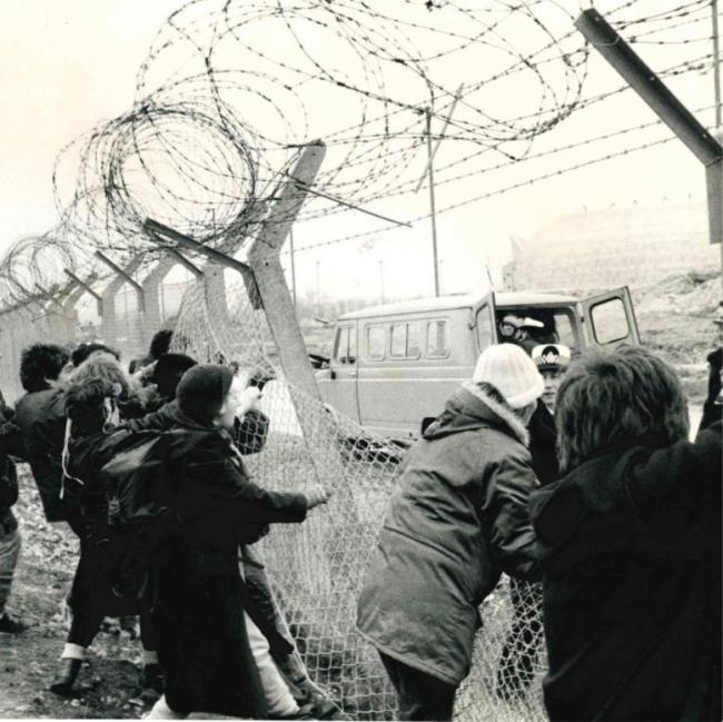 Peace demonstrators pull at the perimeter fence at the Upper Heyford American nuclear bomber base