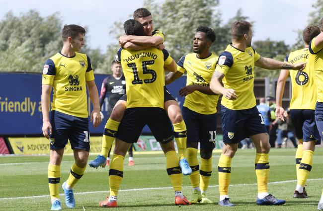 Oxford United captain John Mousinho congratulates goalscorer Cameron Brannagan  Picture: David Fleming