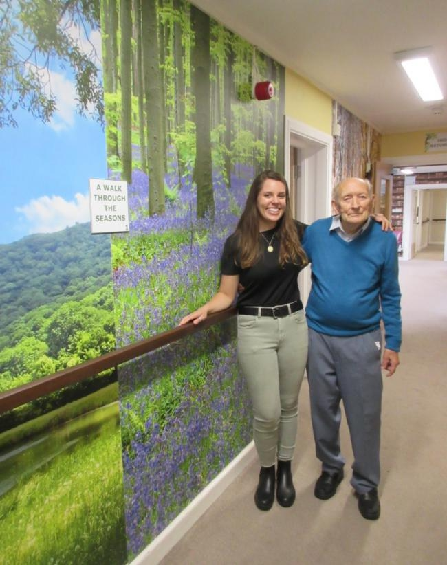 Julia Glassman and one of the residents Bill Tolley in front of the season murals at Marston Court care home