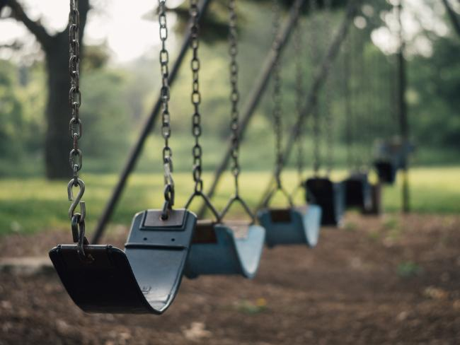 Children's swings in a play park. Stock picture