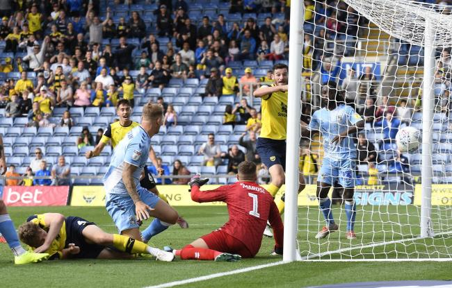 Elliott Moore forces Fankaty Dabo into a second own goal in stoppage time as Oxford United hit back to draw 3-3 against Coventry. The visiting defender had also levelled for the U's earlier in the gamePicture: David Fleming