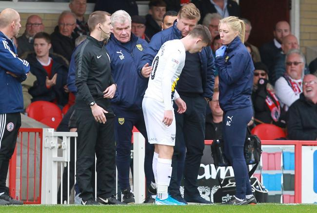 Ben Woodburn's injury is assessed on the touchline with Oxford United boss Karl Robinson   Picture: Richard Parkes