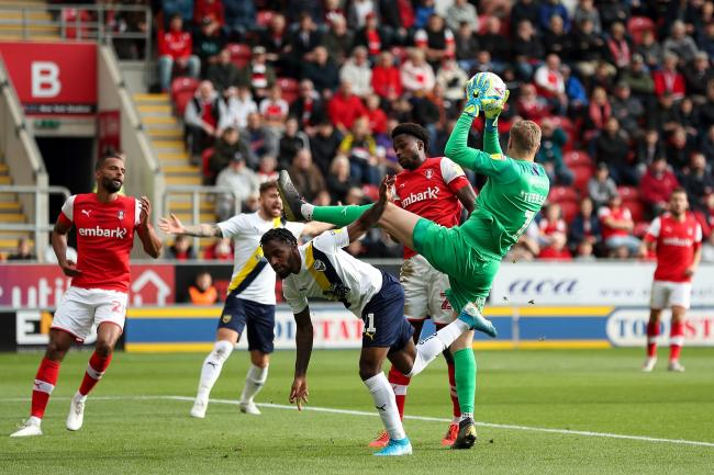 Rotherham goalkeeper Daniel Iversen catches a cross above Tariqe Fosu in the first half  Picture: James Williamson