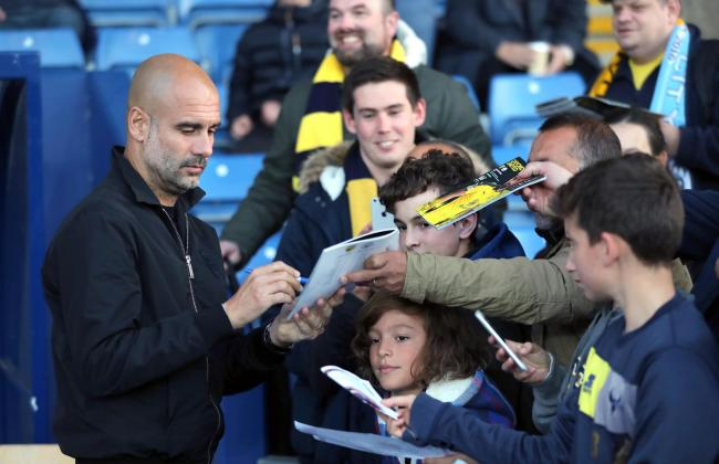 Manchester City manager Pep Guardiola signs autographs for Oxford United fans before last season's game  Picture: Andrew Matthews/PA Wire