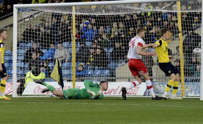 Oxford United's players are helpless to prevent Richard Wood putting Rotherham United 3-0 up before half-time  Picture: David Fleming