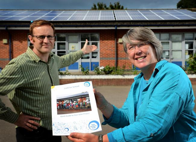 Low Carbon Hub chief executive Barbara Hammond at Larkrise Primary School, east Oxford, with teacher Ed Finch and the hub's solar pane array on the school roof. Picture: Richard Cave