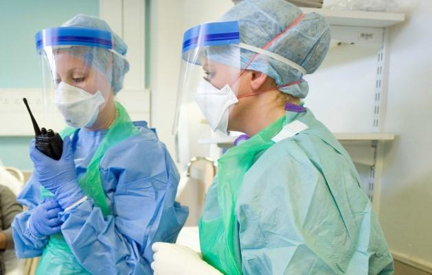 Library picture of doctors at work in full PPE