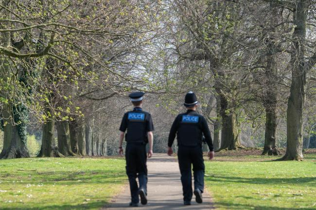 Police officers patrol a park