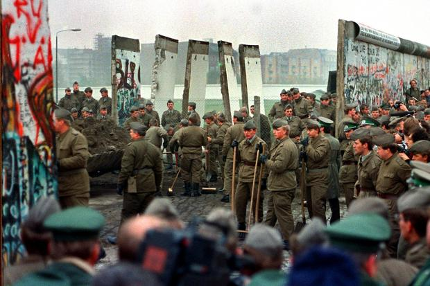 East German soldiers and West German soldiers remove some of the first sections of the Berlin Wall at Potsdammer Platz. (Photo by John Tlumacki/The Boston Globe via Getty Images).