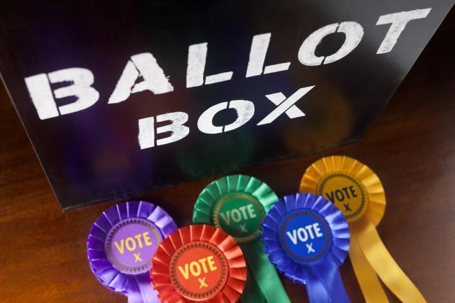 Time to cast your vote in a UK Election. A Ballot Box with coloured rosettes for the principal UK political parties.