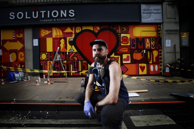 Luke Embden with the mural he has been designing in Oxford's George Street. Picture: Ed Nix