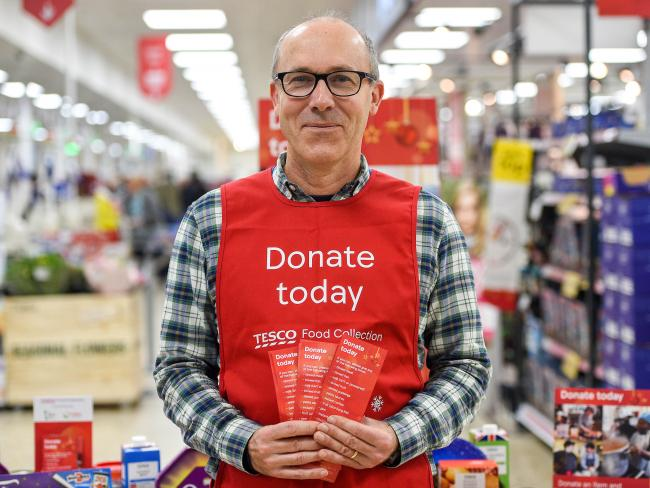 London, UK. 21 November, 2019. A Tesco volunteer holding a shopping list guide for donations at the launch of the Tesco Food Collection in the Surrey Quays Extra store.