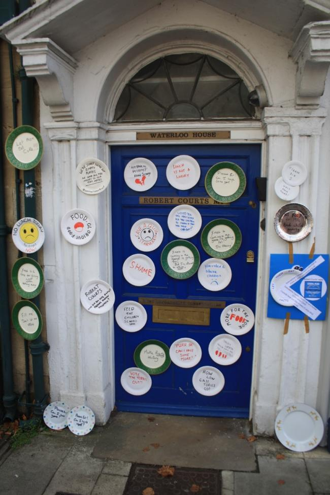 Paper plates on Robert Courts' business address door in Witney