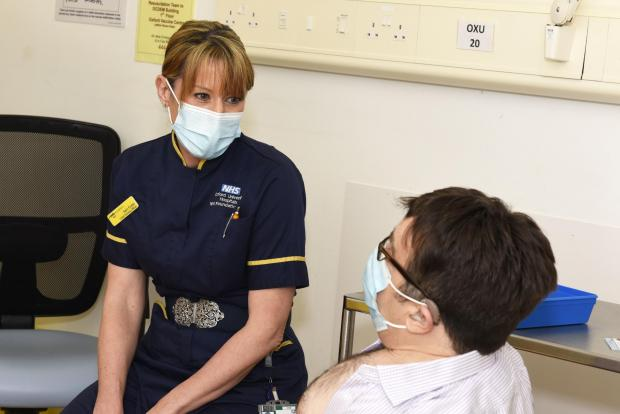 Oxford Mail: Sam Foster, Chief Nursing Officer, and Nicholas Woodthorpe, the first patient at the OUH Vaccination Centre. Picture: Oxford University Hospitals