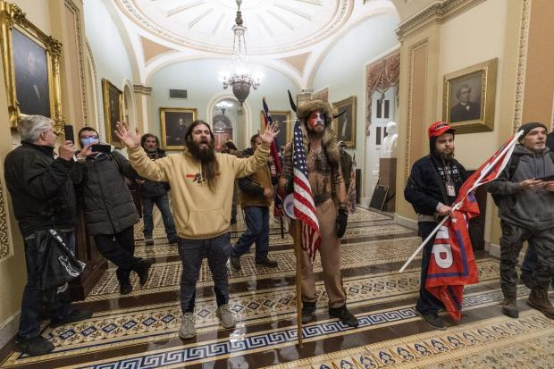 Supporters of President Donald Trump are confronted by U.S. Capitol Police officers outside the Senate Chamber inside the Capitol. AP Photo/Manuel Balce Ceneta).