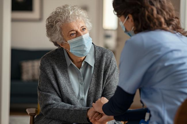 Elderly woman talking with a doctor while holding hands at home and wearing face protective mask. Worried senior woman talking to her general pratictioner visiting her at home during virus epidemic. Doctor explaining about precautionary measures during