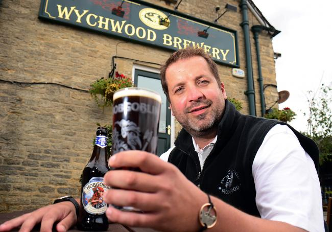 Wychwood Brewery head brewer Jon Tillson with a pint of Hobgoblin. In the background is the original sign. Picture: Wychwood Brewery