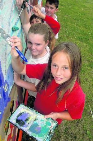 Alicia Higgs, 11, front, and Amberley Castle, 11, behind her, work on the mural
