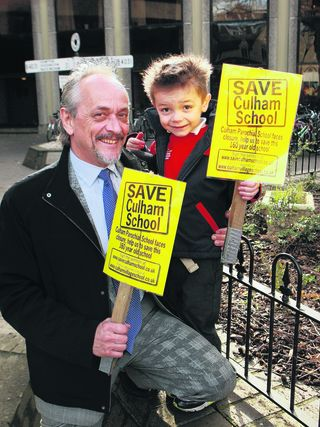Chairman of the campaign group Kitson Thomas with his son Caden demonstrate outside County Hall in Oxford to try to save their village primary school