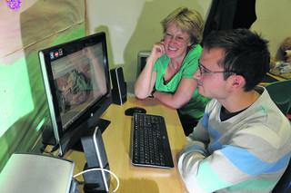 Guidepost Trust organiser Jackie Goodwin watches Chris Carter, 24, on the computer