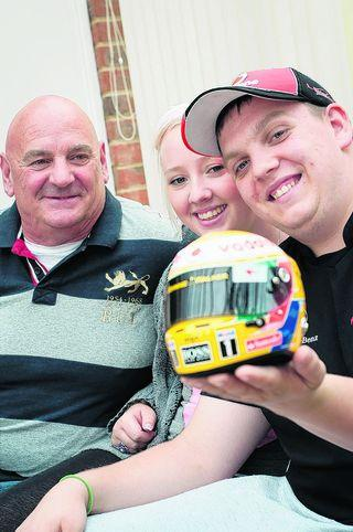 Charlie Leach, right, holding a replica of his favourite Formula 1 driver Lewis Hamilton's helmet, with father David and girlfriend Tiegan Towns