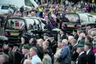 Members of the crowd place flowers on the hearses as they pass through the memorial garden in Carterton