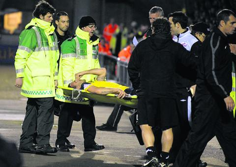 Oxford United assistant manager Mickey Lewis (back to camera) looks on as Peter Leven is stretchered off at Northampton on Friday night – but the midfielder's injury may not be as serious as first feared