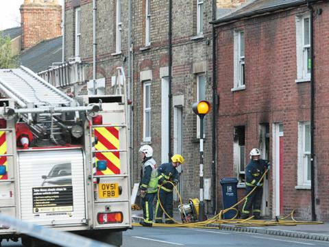 Fire crews clean up after a blaze on Cowley Road.