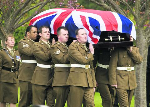 Army pall-bearers carry the Union Flag-draped coffin of L Cpl Michael Foley, right, to his grave at Didcot Cemetery yesterday