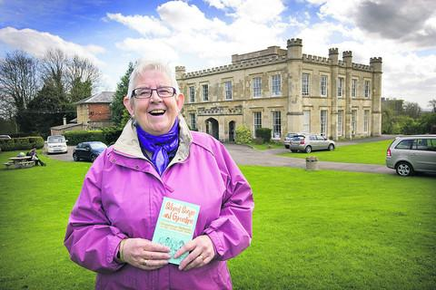 Author Marilyn Yurdan with a copy of her book outside Wheatley Park School – formerly Holton Park Girls' Grammar School
