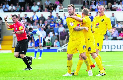 Alfie Potter (No 15) is congratulated by Oxford United teammates Sean Rigg (left) and James Constable after making it 2-0 at Bristol Rovers on Saturday