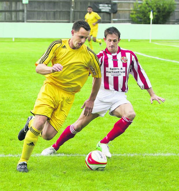 Abingdon United's Matthew Biddle tries to get past Evesham's Jamie Hyde