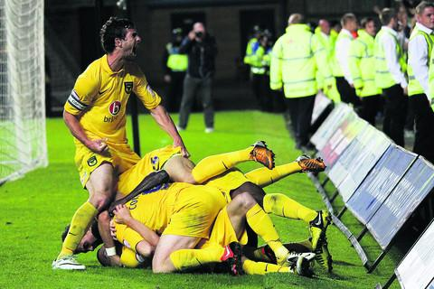 Jake Wright (left) celebrates United's derby goal as his teammates mob Alfie Potter  Picture: Ric Mellis