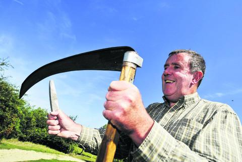 Instructor Clive Leeke sharpens his scythe