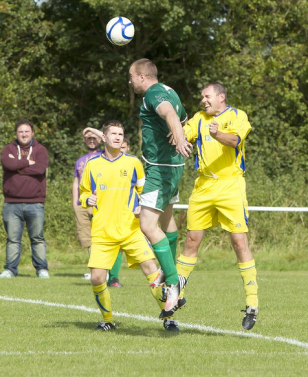 Oxford Irish's Craig Hanlon gets above Andy Gledhill during their 2-2 draw against Launton Sports in the Premier Division