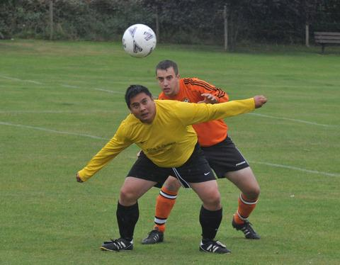 King & Queen Wheatley's Guy Lowe heads forward under pressure from Crowmarsh's Carl Gordon during their Division 1 clash