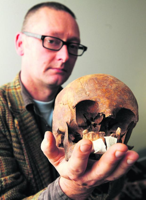 Archaeologist Gwillym Williams with one of the skeletons recovered from the site of the Chapel Street eco-home project