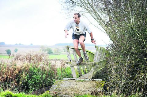 Paul Fernandez crosses a footbridge over the River Evenlode as he nears the finish