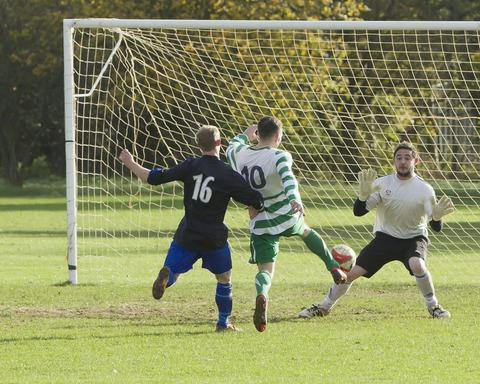 West Witney goalkeeper Danny Rayfield is about to save from Hailey's Craig Mays with the help of a little push from Danny Brearley