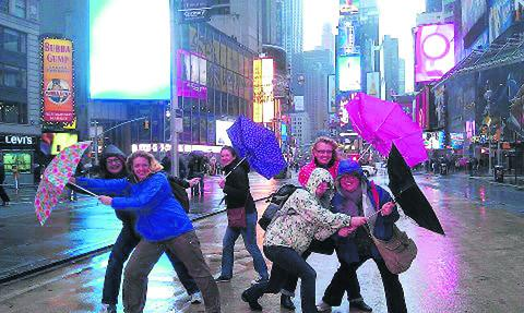Clare Colwell, holding the pink umbrella, and friends in Time Square, New York
