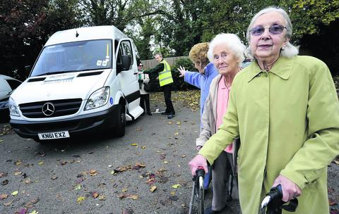 Elia Brown, 85, pictured by the minibus, gets ready to set off on her journey to Sainsbury's while her friends, from left, Maggie Roman, 85, Barbara Dodd, 88 and Violet Lee, 78, miss out again on the bus ride