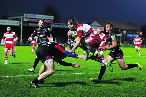 Oxford Mail: Gloucester's Steph Reynolds jumps a tackle from London