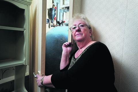 Yvonne Ryman opens the door to the air heating fan system she claims has caused her electricity bill to rocket