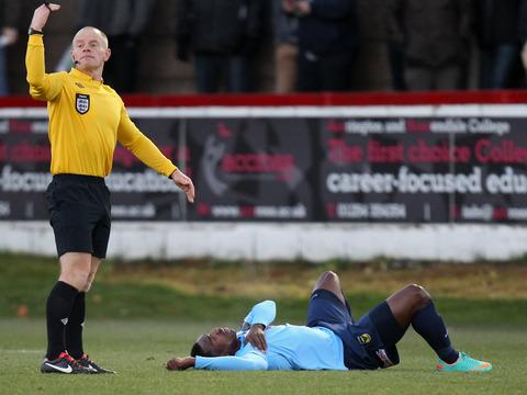 Referee Andy Woolmer calls for help for JP Pittman at Accrington on Saturday