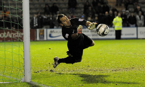 Ryan Clarke pulls off one of his two stops in the penalty shootout that sealed Oxford United's place in the a