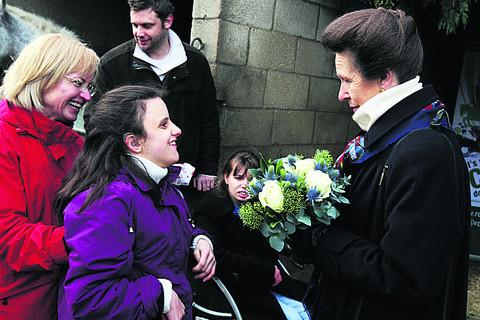 Anna Zaloga, helped by her mum Jadwiga Zaloga, hands some flowers to the Princess Royal