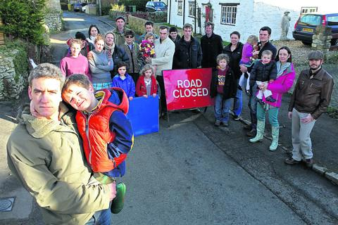 Adrian Porter and son Rowan, four, with residents of Manor Road, South Hinksey, who are taking on Thames Water over their response to flooding in the village