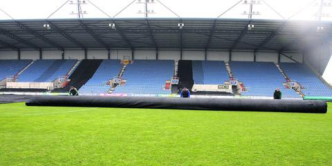 Groundstaff cover the Kassam Stadium pitch yesterday in a bid to ensure that tonight's FA Cup tie with Accrington Stanley goes ahead